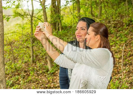 Beauty two eomen friends taking selfie photo in forest