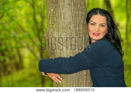 Cose up of smiling woman embracing a tree in forest