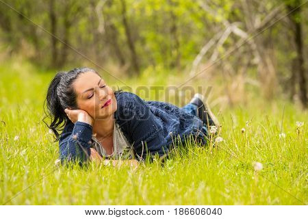 Beautiful woman resting in nature and laying on grass in sunny day