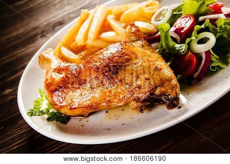 Roast chicken leg with french fries on wooden table