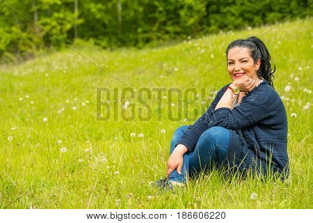 Cheerful female sitting on grass in nature in sunny day