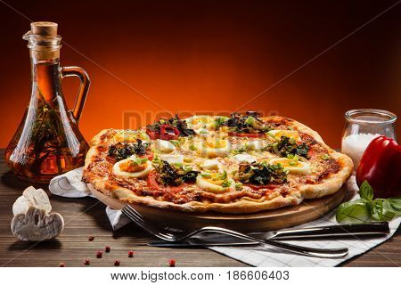 Pizza pepperoni with egg on wooden table