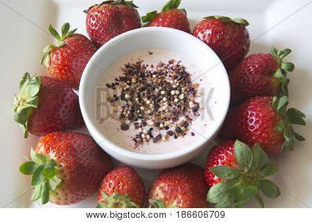 Greek strawberry yoghurt in a bowl with a superfruit topping of dried blueberries, hibiscus, chia seeds and airy quinoa pops surrounded by delicious strawberries