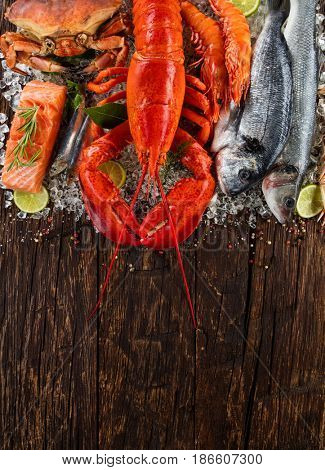Whole lobster with seafood, crab, mussels, prawns, fish, and other shells served on crushed ice and wooden table