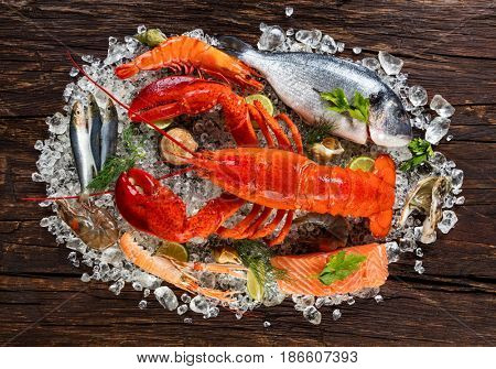 Fresh seafood, lobster, crab, mussels, prawns, fish, crab, salmon steak, bream fish and other shells served on old wooden table