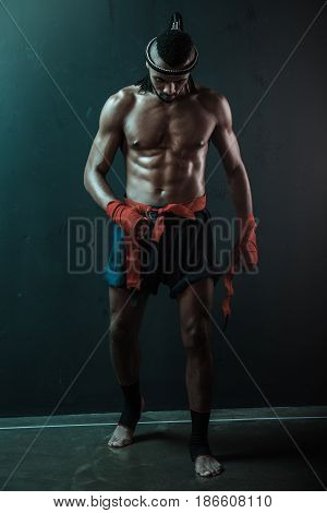 Full Length View Of Muscular Muay Thai Athlete Looking Down Indoors, Action Sport Concept