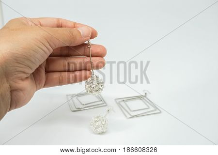 isolated close up women hold cute creative earring with left hand for party