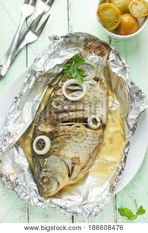 Baked in foil whole fish carp with onion