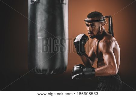 Determined Young Muay Thai Fighter In Boxing Gloves Training Thai Boxing With Punching Bag, Boxing G