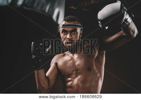 Determined Young Muay Thai Fighter In Boxing Gloves Training Thai Boxing With Punching Bag, Action S