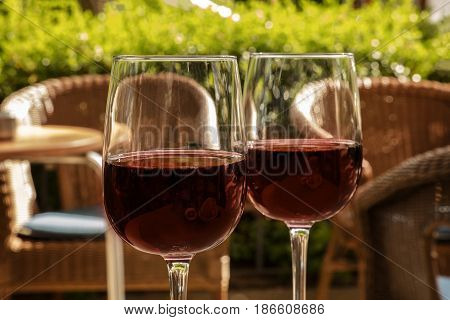 Two glasses of red wine on a terrace, on a blurred background of rattan chairs and green plants. Selective focus