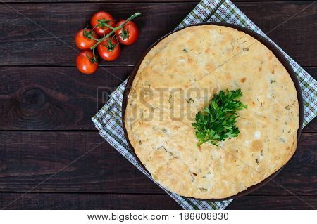 A thick flapjack - pita bread with greens on a dark wooden background. A traditional Asian dish. The top view