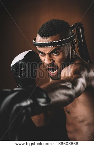 Aggressive Young Muay Thai Fighter In Boxing Gloves Training Thai Boxing, Action Sport Concept