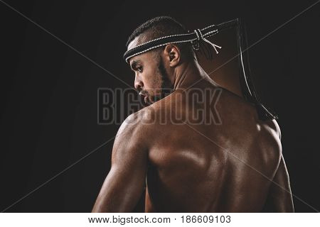 Back View Of Muscular Shirtless Muay Thai Fighter Looking Over Shoulder, Action Sport Concept