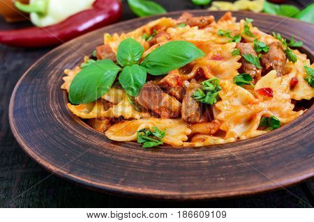 Pasta farfalle with chicken tomato sauce and basil in a clay bowl on dark wooden background. Close up