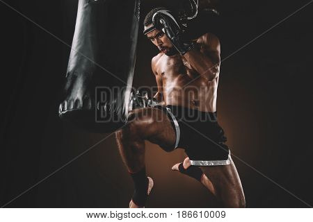 Focused Muay Thai Fighter Training With Punching Bag, Action Sport Concept