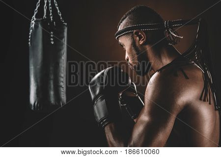 Side View Of Focused Muay Thai Fighter In Boxing Gloves