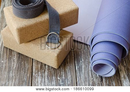 Close up of Accessories or props for yoga pilates or fitness. Exercise lilac mat two cork blocks and grey strap on wooden background.