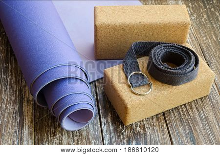 Accessories or props for yoga pilates or fitness. Exercise lilac mat two cork blocks and grey strap on wooden background.