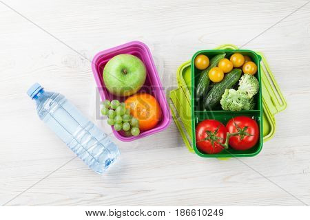 Lunch box with vegetable and fruits on wooden table. Top view