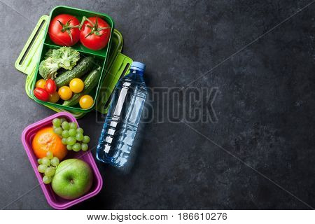 Lunch box with vegetables, fruits and water bottle. Kids take away food box. Top view on blackboard with space for your text