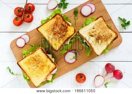 Multilayered sandwiches with a juicy cutlet cheese radish cucumber lettuce arugula on a cutting board on a white wooden background. Top view.