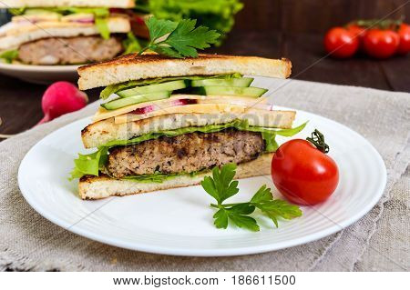 Multilayered sandwiches with a juicy cutlet cheese radish cucumber lettuce arugula cutting in half on a plate on a dark wooden background. Close up