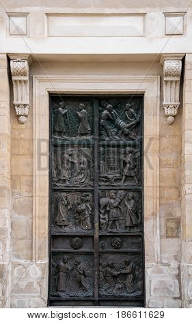 A metal church door with images from the stations of the cross