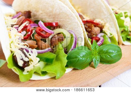 Tacos is a traditional Mexican dish. Tortilla stuffed with chicken bell and hot peppers beans lettuce cheese blue onion with salsa sauce on white wooden background. Close up