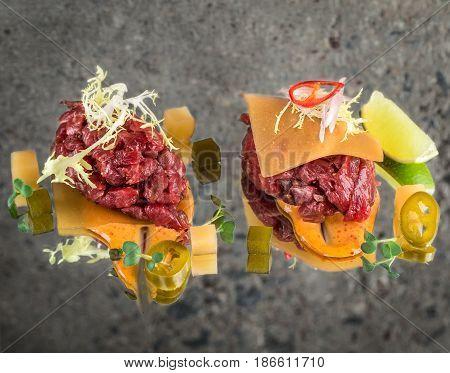 Fresh beef tartar with garnish over concrete background