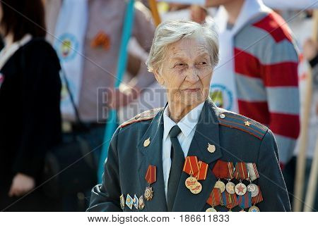 Yekaterinburg, Russia - 9 May, 2017: Old woman - officer, major veteran of the Great Patriotic War decorated with medals. Watching the parade. Victory Day.