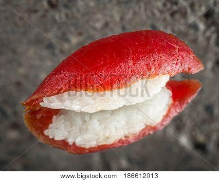 Nigiri sushi with marinated tuna over concrete background
