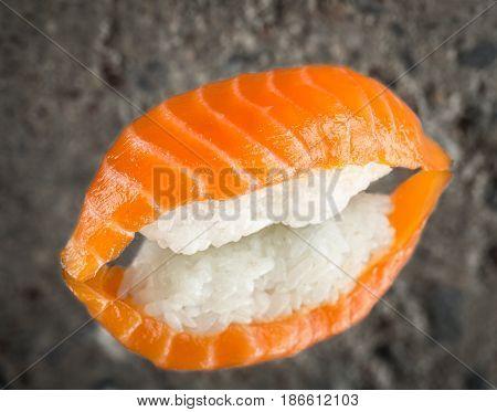 Nigiri sushi with marinated salmon over concrete background