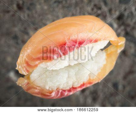 Nigiri sushi with marinated sea bass over concrete background