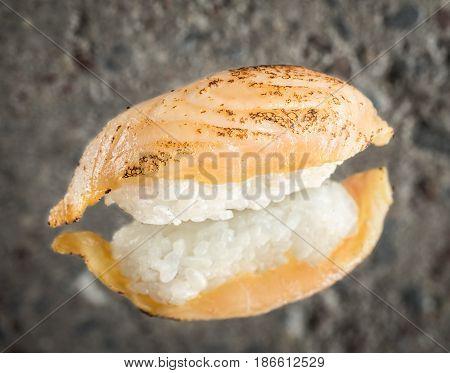Burned nigiri sushi with sea bass over concrete background