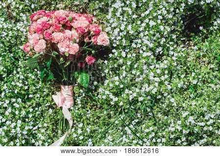 wedding bouquets of biege carnations and pink roses on grass full of small blue flowers
