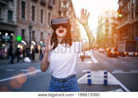Young brunette is amused by her first encounter with futurist virtual reality glasses which alter the busy world around her