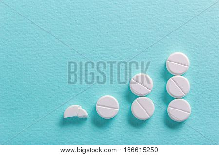 White round pills on a green background. Increase the dosage of the medicine. Growing diagram up. Empty place for text copy paste