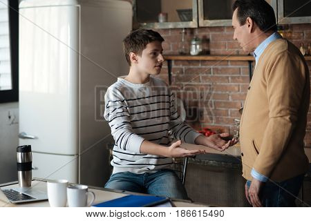 Believe me. Positive delighted boy holding hands in the air and sitting opposite his father while having conversation