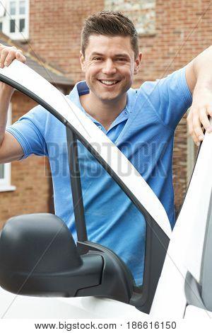 Outdoor Portrait Of Smiling Driver With Van