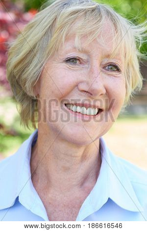 Head And Shoulders Portrait Of Senior Woman In Garden