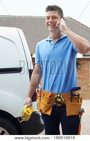 Electrician With Van Talking On Mobile Phone Outside House
