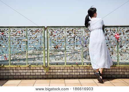 Young beautiful japanese woman stays and leans on fence