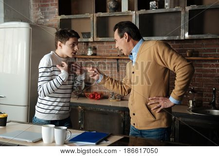 It is a lie. Angry male person putting left hand on the belt and keeping mouth opened while pointing at his son