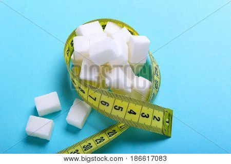 Sugar cubes in a measuring tape on a blue background. Diet without sugar