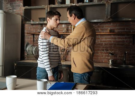 Low spirits. Serious male person standing in semi position and putting both hands on the shoulders of his son while supporting him