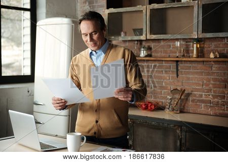Correct mistakes. Positive father keeping smile on face bowing head while looking downwards at sheet of papers