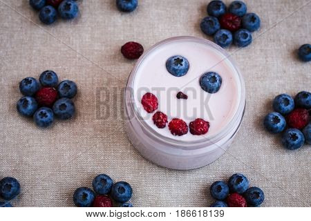 blueberry yogurt with berries smile face creative food chid breakfast top view flat lay