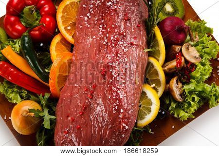 Fresh raw beef with vegetables on cutting board isolated on white