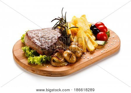 Grilled beefsteak with french fries and mushrooms on wooden desk on white background